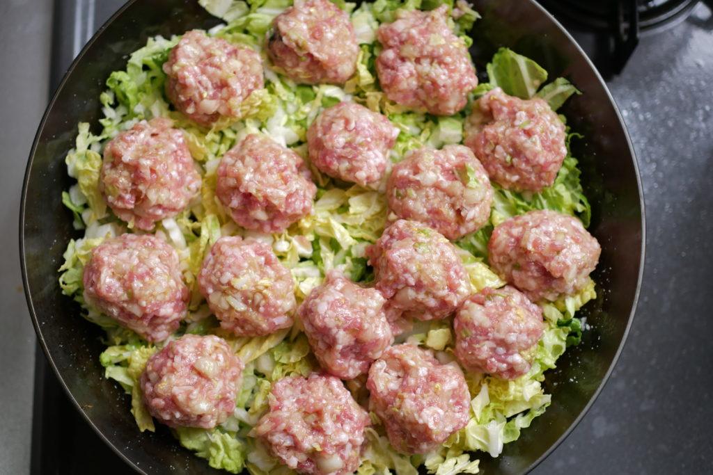 フライパンへ白菜をひいて、タネを丸めて並べる